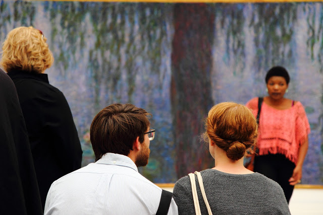 """Due ragazzi intenti ad ammirare """"Le ninfee"""" di Monet al Mudeo de l'Orangerie a Parigi"""