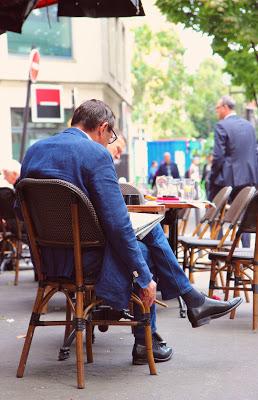 Signore seduto nel dehor di un bistrot a Parigi